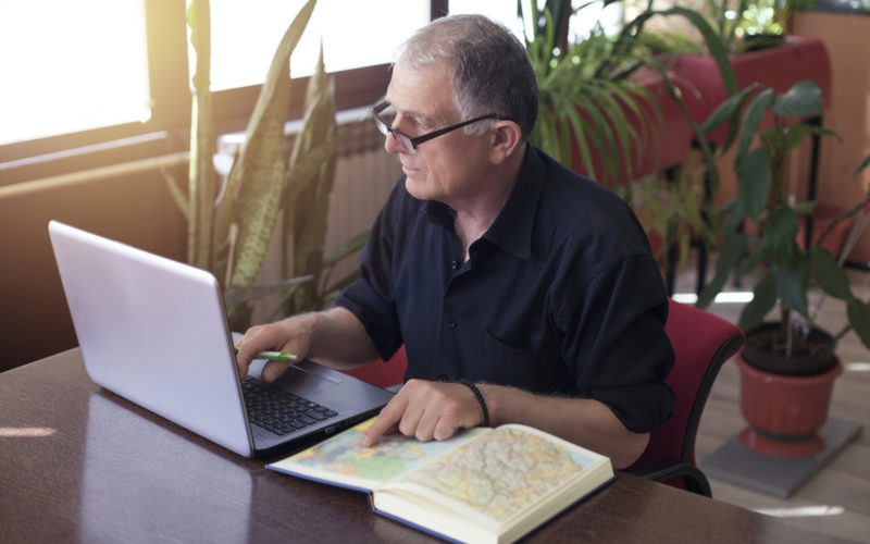 Man With Map Book And Computer